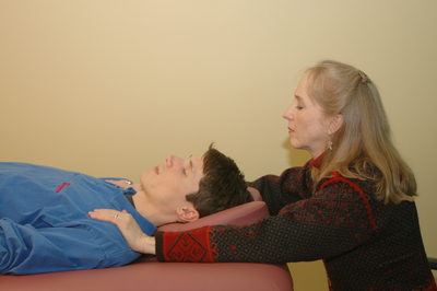reiki practitioner placing her hands on the shoulders of a client, who is lying down