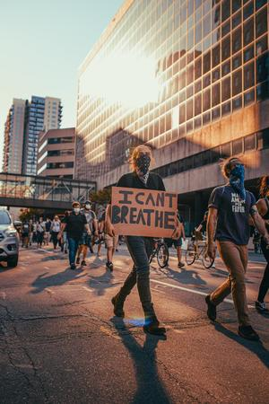 people protesting on a street carrying a sign that says I Can't Breathe