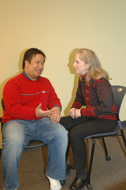 seated man talking to reiki practitioner