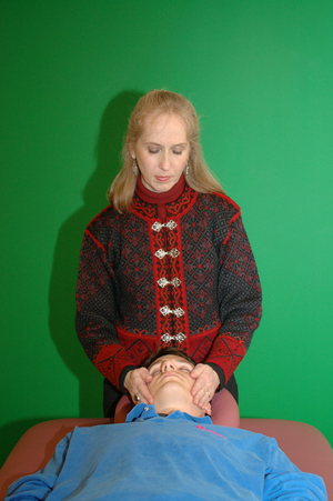 reiki practitioner placing her hands on the head of a client, who is lying down
