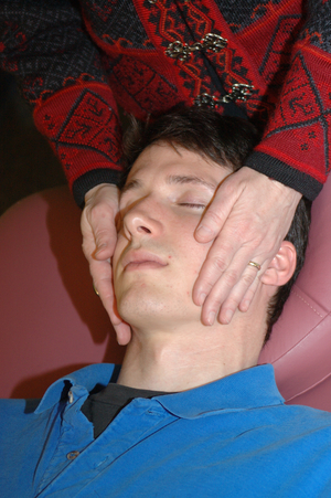 close up of a man's relaxed face as he receives reiki on his cheeks
