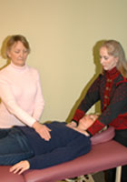 Two people practicing Reiki on a third