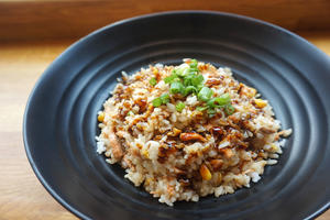 bowl of cooked brown rice with green onion on top