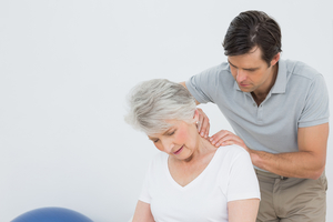 Chiropractor rubbing neck of senior female patient