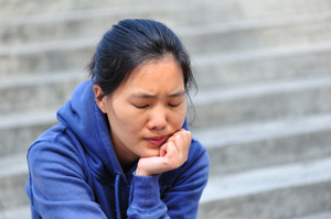 stressed woman sitting with chin in hand