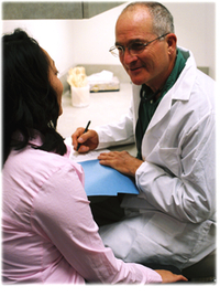 healthcare provider in white coat listening to patient and taking notes