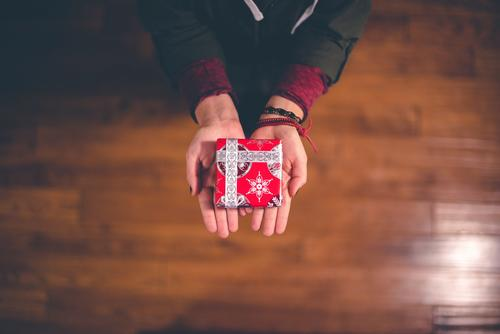 hands holding a small gift wrapped in red paper