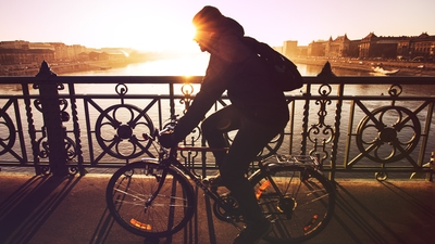 man bicycling across a city bridge in the morning