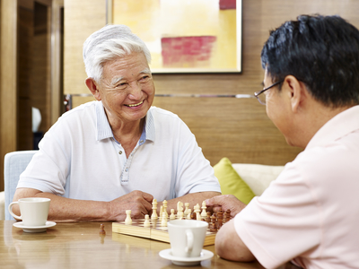 Elderly man smiles as he plays chess with a friend
