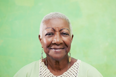 smiling elderly woman against a green background