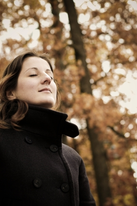 woman with eyes closed breathing deeply outdoors
