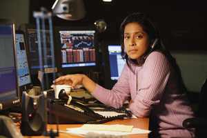 woman sitting at work desk with headset and several computers