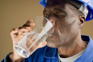 Construction worker drinking a glass of water