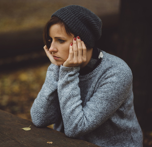 depressed woman sitting at a picnic table in the woods