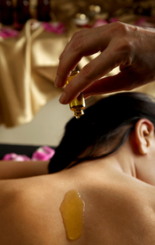 hand pouring essential oil on a woman's bare back