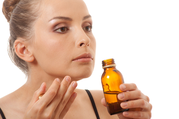 woman smelling a bottle of essential oils