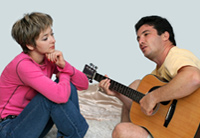 Man plays guitar, therapist listens