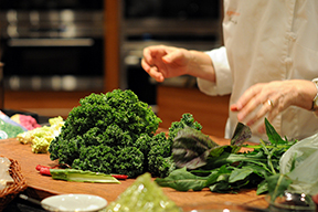 Close up of a chef's hands preparing leafy greens