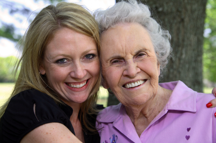 Smiling young woman hugging elderly woman.