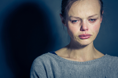anxious woman crying in front of a blue background