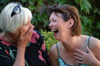 Two middle-aged women laughing together.