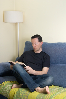 Man reading a book on couch.
