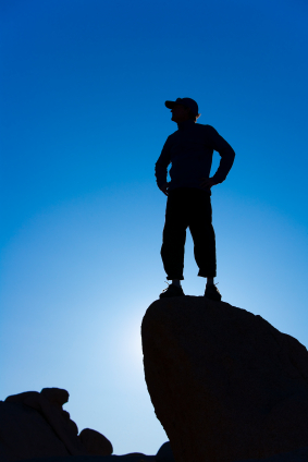 Brave man standing on rock and looking out over landscape.