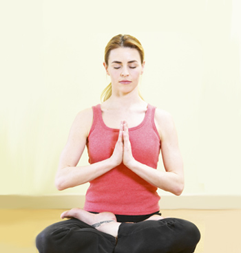 Woman meditating in lotus position.