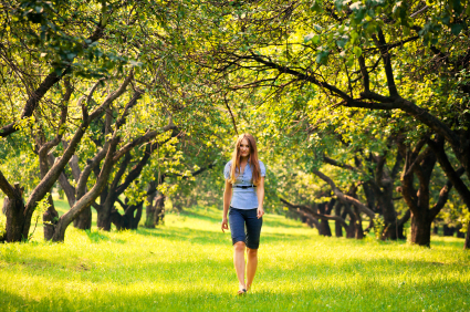 Woman walking through a beautiful green park.