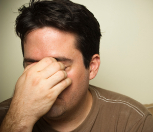 man with eyes shut, touching his forehead in stress
