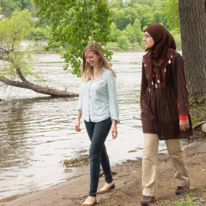 two women walking by river