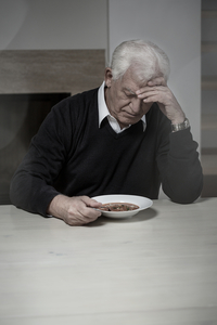 lonely older man eating soup alone
