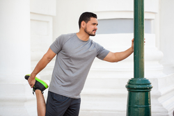 man leaning against a pole outside and stretching his leg before running
