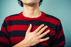 close up of man's torso, wearing a striped sweater. his hand is over his heart