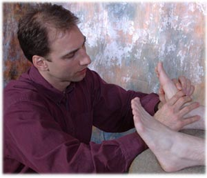reflexologist touching a patient's feet