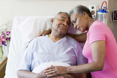 elderly patient in hospital bed with wife next to him