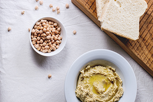 bowl of hummus next to a bowl of chickpeas