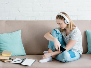 girl sitting on couch listening to music