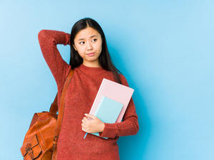 student holding books and bag looking pensive and uncertain