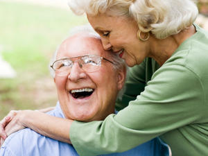 two elderly people laughing and hugging