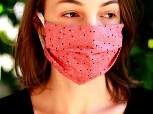 woman wearing a pink face mask