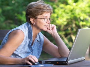 middle aged woman using laptop outside