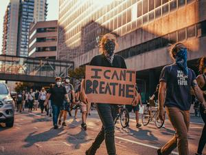 people marching in the streets, one carrying a sign that says I Can't Breathe