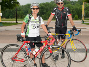 Two bicyclists in biking gear and helmets smile