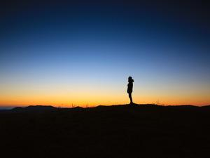 a lone silhouette standing in front of a sunset