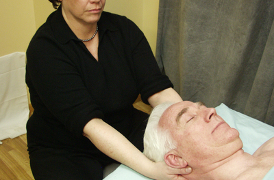 masseuse holding a man's head as he lay on the table