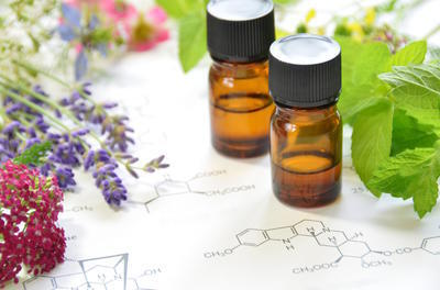 two unlabeled brown bottles of essential oils with black caps on a chemistry paper with leaves and flowers around the edges