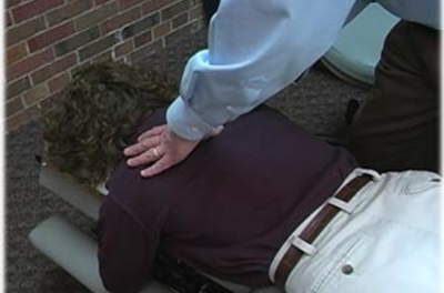 Chiropractor's hands on a female patient's back