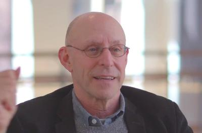Still of Michael Pollan speaking to the camera in front of a light background