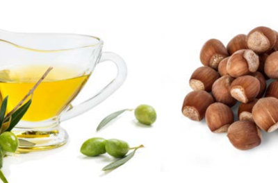 Container of oil and small pile of nuts on a white background